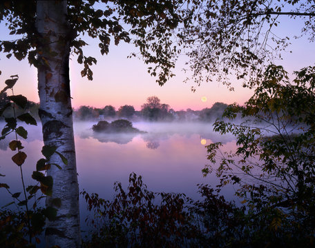 USA, Maine, Pittsfield. Moonset at sunrise with fog rising over Mill Pond.