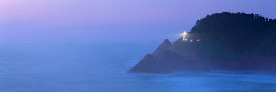USA, Oregon, Heceta Head. The beacon of Heceta Head Lighthouse shines through the periwinkle blue fog on the Oregon Coast.