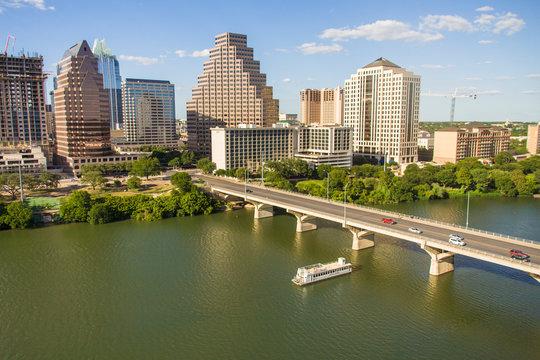 USA, Austin, Texas, Downtown Skyline with Cruise Boat on Lady Bird Lake, Colorado River crossing under the Bat Bridge.