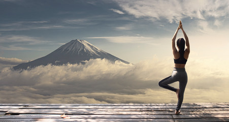 Young woman practicing yoga in the nature. female happiness. Landscape background. Fototapete