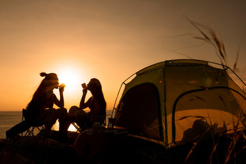 Two asian female hikers sit by tent during sunset. Fototapete