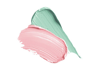 Color corrector strokes isolated on white background. Green and pink color correcting cream concealer smudge smear swatch sample. Makeup foundation creamy texture