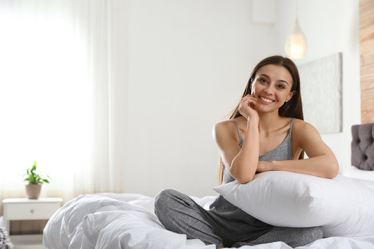 Portrait of beautiful young woman sitting on large bed