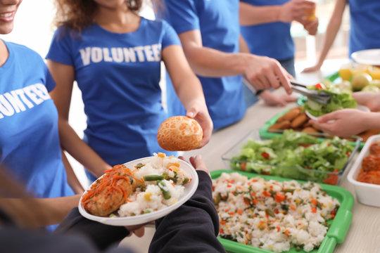 Volunteers serving food to poor people, closeup