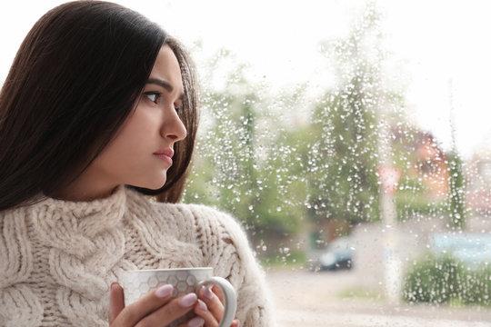Sad beautiful woman with cup near window indoors on rainy day