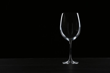 Acrylic Prints Alcohol Empty wine glass on table against black background, space for text
