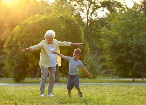 Little boy and his grandmother having fun in park