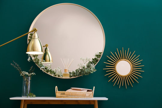 Round mirror and table with accessories near green wall in modern room interior