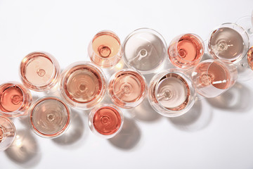 Spoed Foto op Canvas Alcohol Different glasses with rose wine on white background, top view