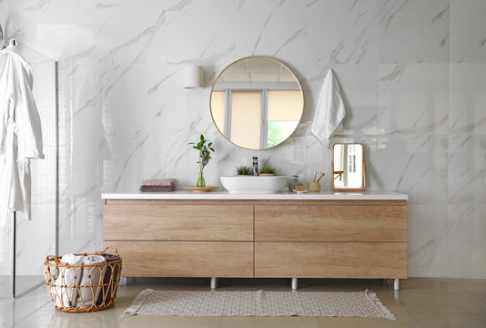 Modern bathroom interior with stylish mirror, vessel sink and glass shower stall