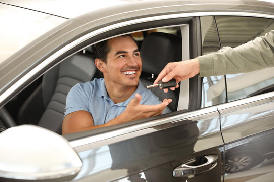 Young salesman giving car key to customer in modern auto dealership, closeup