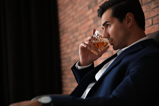 Young man with glass of whiskey near brick wall indoors. Space for text