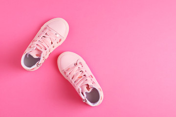 Wall Mural - Pair of stylish child shoes on pink background, flat lay. Space for text