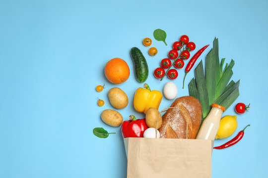 Shopping paper bag with different groceries on light blue background, flat lay. Space for text
