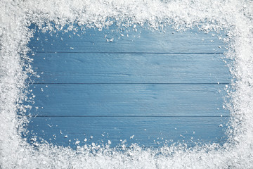 Fotobehang - Frame of white snow on blue wooden background, top view with space for text. Christmas season