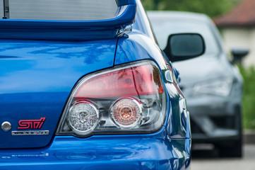 closeup of rear light of blue Subaru imprezia parked in the street