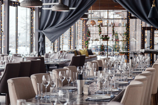 Christmas lights, decor, interior modern restaurant, panoramic windows, setting, serving banquet, gray textile chairs, serving tables, wine glass, plates, cutlery. Concept festive new year, winter