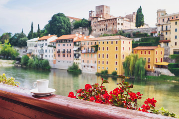 Vacations in Italy. Cup of coffee on a balcony with beautiful italy town on the background. Bassano del Grappa, Veneto region, Italy.