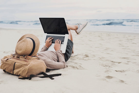 Young woman using laptop computer on a beach. Freelance work, distance learning, vacation concept