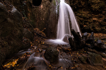 Waterfall in the woods in Pale (Umbria, Italy) with autumn leaves on the ground