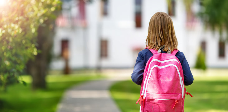 Girl with rucksack infront of a school building