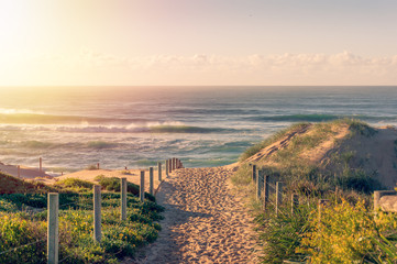 Entrance to the beach with beautiful waves at sunrise