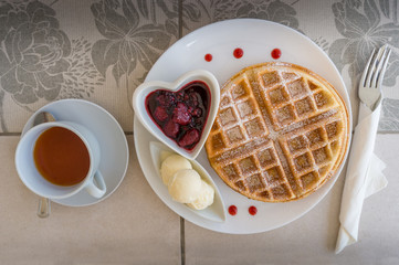 Top view of table setting with belgian waffles, ice cream and jam with tea