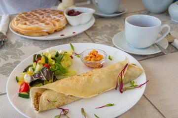 Breakfast, light meal table setting with crepe wrap, salad and Belgian waffles