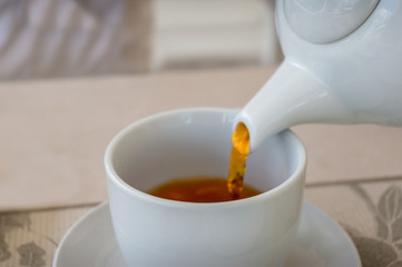 Close up of tea pouring in a white tea cup