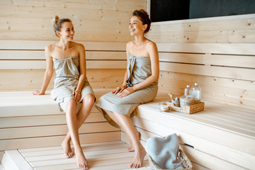 Two girlfriends relaxing in the sauna