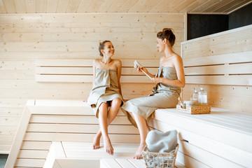 Two girlfriends relaxing in the sauna