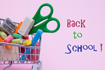 Shopping cart with different stationery on an pink background, back to school concept