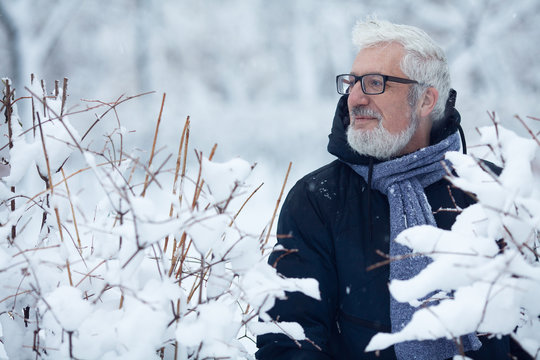 Active grandpa concept. Portrait of handome mature man in trendy winter clothing and fashionable glasses standing near bushes, over snow park background. Close up. Text-space.  Outdoor shot