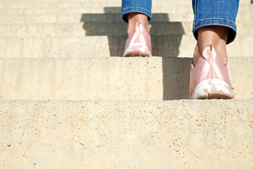 Optimistic conceptual image of young woman, back view of volonteer wearing pink sneakers with breast cancer awareness ribbon climbing up the stairs. Background, close up, copy space.