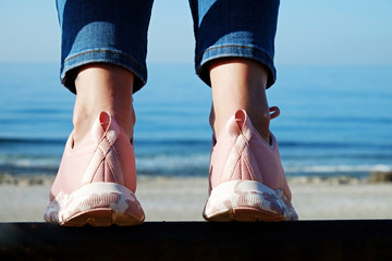 Optimistic conceptual image of young woman, volonteer wearing pink sneakers with breast cancer awareness ribbon standing on the beach. Background, close up, copy space.
