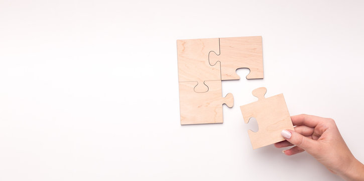 Woman creating wooden puzzle of four pieces with copy space