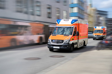 two emergency ambulances are driving fast with blue flashing light through the city, panned shot with motion blur Wall mural