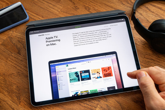 Paris, France - Jun 6, 2019: Man reading on Apple iPad Pro tablet about latest announcement of at Apple Worldwide Developers Conference WWDC - showing the Apple TV on Mac