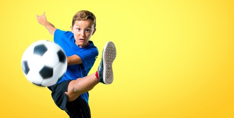 Boy playing soccer kicking the ball on yellow background