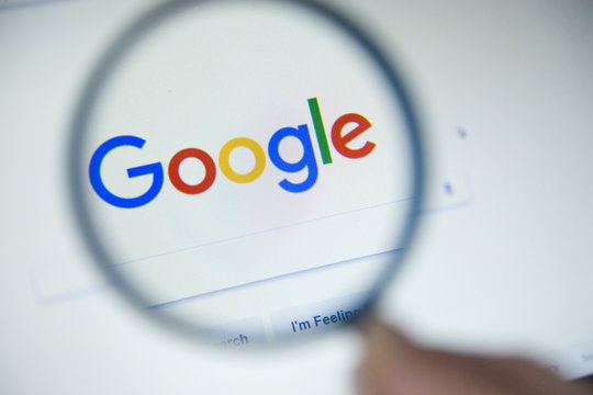 Paris, France - October 19, 2017 : Google.fr homepage on the screen under a magnifying glass. Google is world's most popular search engine