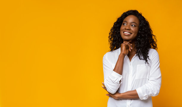 Young afro girl dreaming on yellow background