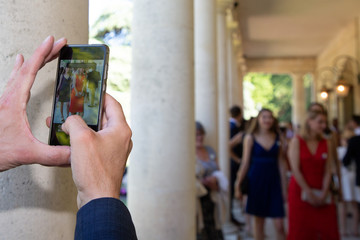 guest at wedding ceremony takes pictures smartphone on the phone