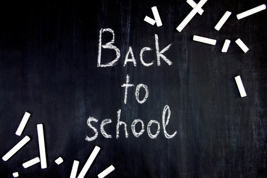 Inscription of back to school on classroom blackboard background. Pieces of white chalk are scattered on black canvas. Preparing pupils students for study at college, university, academy.