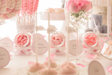 Various sweets on a lovely pastel pink candy bar at the wedding party