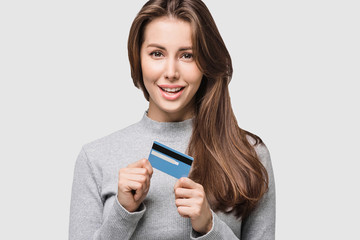 Young woman holding credit card. Isolated on grey background. Studio shot. Online shopping, e-commerce, internet banking, spending money, enjoying life concepts