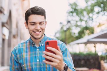 Young handsome student man using smartphone in a city. Cheerful men holding mobile phone. Technology, connection, communication concept