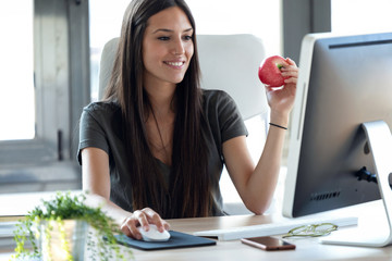 Wall Mural - Smiling young business woman eating a red apple while working with computer in the office.