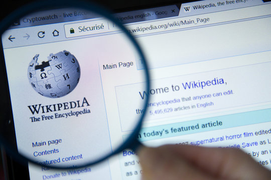 Paris, France - October 19, 2017 : Wikipedia homepage on the computer screen under magnifying glass. Wikipedia is a free Internet encyclopedia.
