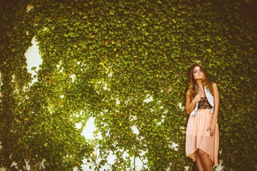 Beautiful brunette in a dress standing by the overgrown wall of greenery Wall mural