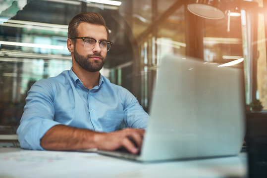 Comfortable working place. Young bearded businessman in eyeglasses and formal wear using laptop while sitting in modern office